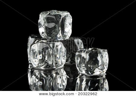 Ice cubes in a pool of water isolated on a black background