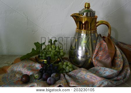 still life in Oriental style with grapes and gold pitcher