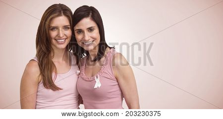 Smiling women in pink outfits posing for breast cancer awareness against neutral background