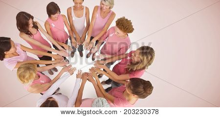 Female friends supporting breast cancer awareness against neutral background