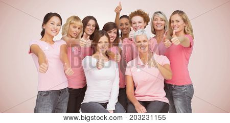 Portrait of female friends showing thums up sign for breast cancer awareness against neutral background
