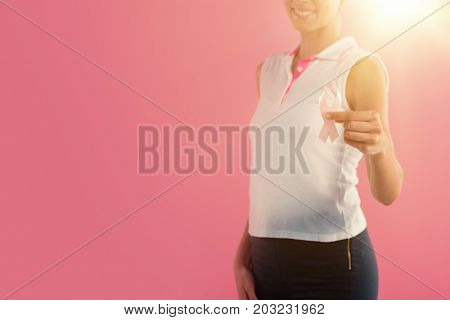 Portrait of pretty woman holding breast cancer awareness ribbon