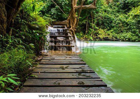 Wooden walkway through waterfall stairs in rain forest .Wooden path walkway through the forest