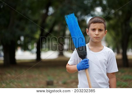 A close-up portrait of a serious little boy standing with a blue broom. A boy in latex gloves cleaning up the trash on a blurred natural background. Ecology, nature pollution concept.