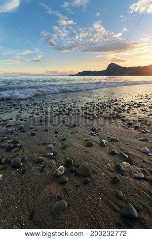 the city of sudak Crimea sunset / evening coastal beach of the calm black sea vacation trip
