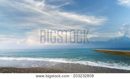 calm black sea pebble beach / turquoise water on the beach on the background of stratus clouds