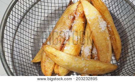French fries has salt on top in grille and aluminum antique plate.