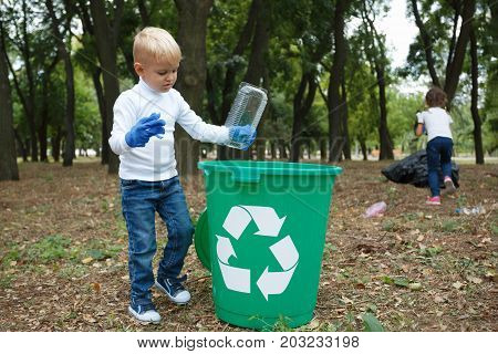 A full-length portrait of a cute little boy putting a plastic container in the recycling container. Child picking up the plastic trash on a blurred natural background. Ecology, nature pollution concept.