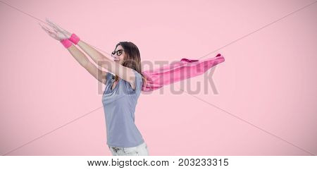 Woman in superhero costume pretending to fly  against pink background