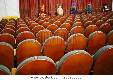 MOSCOW - OCT 19, 2016: Rows of seats in empty theater and puppets on chairs on stage with closed curtain in Modern theater