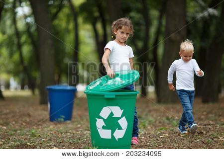 A full-length portrait of a cute little girl putting a bucket lid on a bright green recycling container. Children collecting the garbage on blurred park background. Ecology, nature pollution concept.