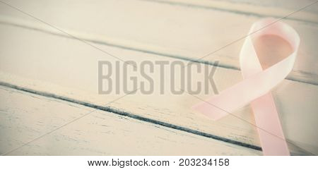 Close-up of pink Breast Cancer Awareness ribbon on white wooden table