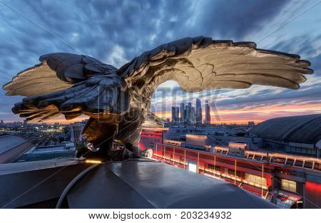 MOSCOW - SEP 19, 2015: Rooftop of Kievsky railway station with eagle sculpture and view of Moscow city skyscrapers