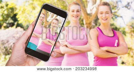 Hand holding mobile phone against white background against portrait of confident volunteers supporting breast cancer social issue