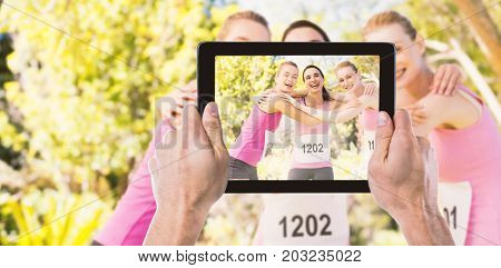 Cropped hand holding digital tablet against portrait of young athlete women forming huddles