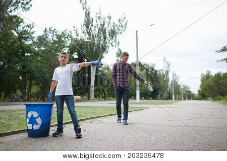 A full-length portrait of a little serious boy and a slovenly young man on a blurred natural background. A child showing thumb down to a guy throwing a bottle in the middle of the road. Copy space.