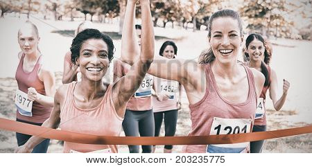 Portrait of happy female breast cancer participants crossing finish line at marathon race in park