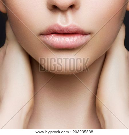Sexual full lips. Natural gloss of lips and woman's skin. The mouth is closed. Increase in lips cosmetology. Pink lips and long neck.