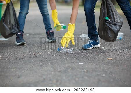 A close-up picture of child's legs and hands in yellow latex gloves. a couple of children picking up the plastic trash. Environment, ecology, nature protection, pollution concept. Copy space.