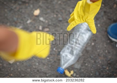 A top view of children's hands in yellow latex gloves. Children picking up the plastic trash, close-up. Environment, ecology, nature protection, pollution concept. Copy space.
