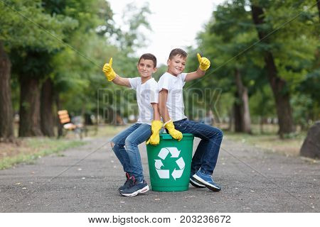 A full-length portrait of children in yellow latex gloves on a blurred park background. A couple of children sitting on a green recycling bin and showing thumbs up. Environment, pollution concept.