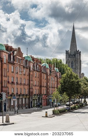Dublin Ireland - August 7 2017: Row of red brick facades in Patrick Street leading to spire of Saint Patrick's Cathedral. Green trees and traffic light. Monumental cloudscape.