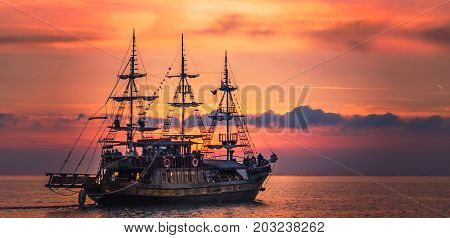 Antique pirate ship leaving the harbor at the sunset