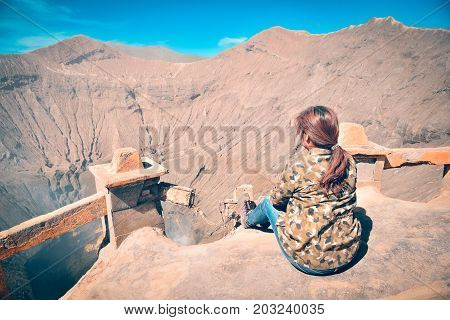 Asain Traveler Women sitting on top of mountain with enjoying beautiful landscape view of Mount Bromo volcano (Gunung Bromo) the most famous tourist attraction in Indonesia.