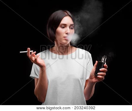 A close-up portrait of a female silhouette smoking a tobacco cigarette or an electronic cigarette on a black background. A girl in a white T-shirt with a smoke cloud. Healthcare, bad habits concept.