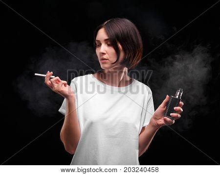 A close-up portrait of a female silhouette smoking a tobacco cigarette or an electronic cigarette on a black background. A girl with an unhealthy habit. Healthcare, bad habits concept.