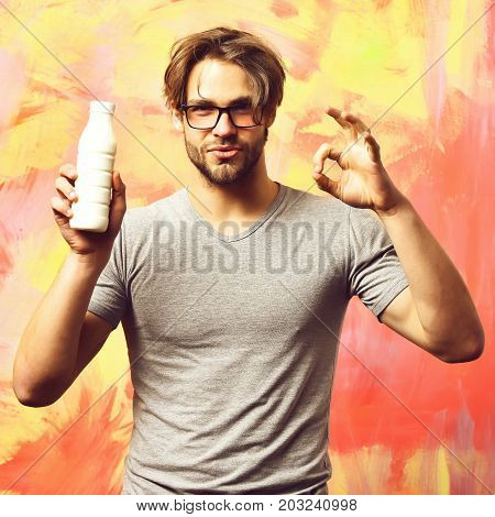 Bearded man short beard. Caucasian sexy satisfied macho with moustache in glasses wearing gray shirt holding plastic bottle of milk showing ok gesture on colorful studio background poster