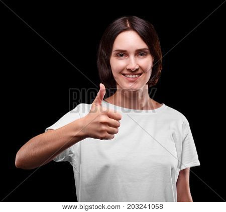 A close-up of a cheerful young lady on a black background. A brunette attractive girl showing a thumb up. A smiling young woman in a white T-shirt. Health, confidence, beauty, freshness concept.