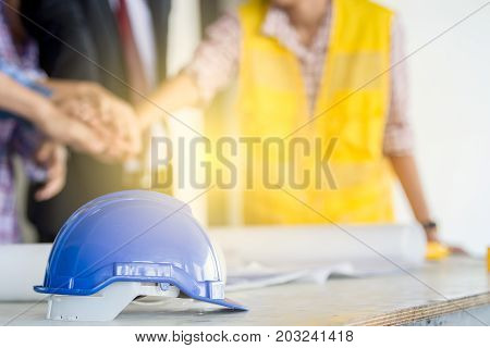 Engineer blue helmet on the table close up with people in the background.