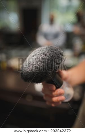 A close-up picture of a big black brush in a white talcum powder on a blurred background. A vintage shaving accessory for barbershops. Tools for cutting a beard. Beauty, style, fashion concept.