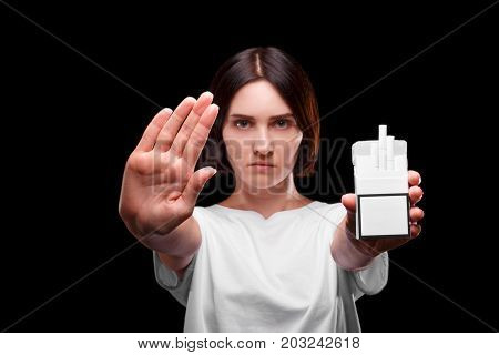 A portrait of a serious female holding a pack of cigarettes on a black background. A young brunette woman showing a stop sign against smoking. Stop smoking. Healthy lifestyle, habits concept.