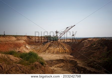 An industrial moving machine in the foundation pit. Yellow mobile crane working in the sandy quarry. Industry equipment on a blue sky background. Technology, cargo, commerce, transport concept.