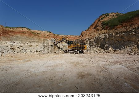 Huge excavator loads the ground on a blue sky and sandy quarry background. Excavator at sandpit during earthmoving works. Technology, cargo, commerce, transport concept. Copy space.