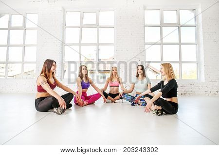 Group of young women doing yoga in the gym. Fitness. The concept of sport dance and a healthy lifestyle.