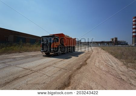 A machinery equipment with a laden ground on a natural sandy quarry background. One massive orange transporter driving on a sandy road. Technology, cargo, commerce, transport concept. Copy space.