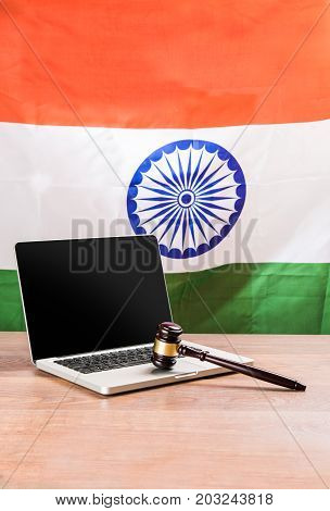 india and cyber law, laptop and wooden gavel or hammer placed over wooden table and indian tricolour or flag in the background showing cyber law in India