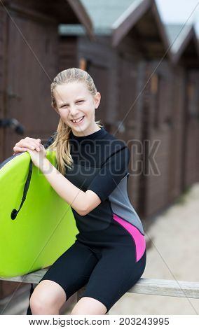 Portrait Of Girl By Beach Huts In Wetsuit Holding Bodyboard