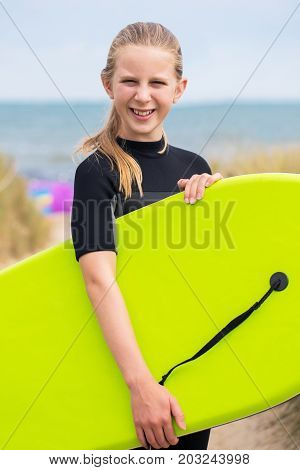 Portrait Of Girl By Sea In Wetsuit Holding Bodyboard
