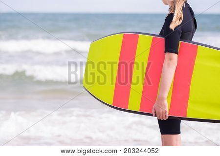Close Up Of Girl By Sea In Wetsuit Holding Bodyboard