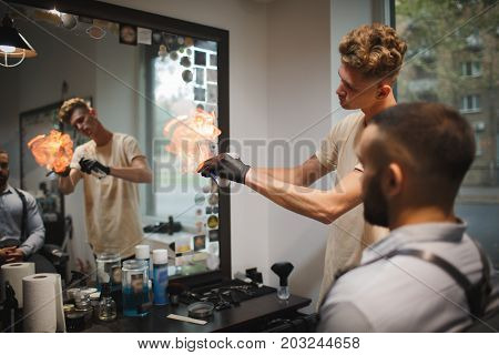 A hairdresser heating the blade of fashioned straight razor under a stream of fire for smoother shaving on a barbershop background. A barber preparing tools for traditional beard shave in the salon.
