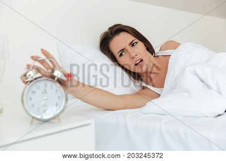 Irritated angry woman laying in bed and holding hand above alarm clock indoors