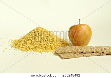 Dietary breakfast. Apple stack of crispbread and a handful of millet on a light background. Focus on the apple and millet.