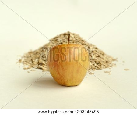 Golden apple close-up on a background of a handful of oat flakes on a light background. Focus on the apple.