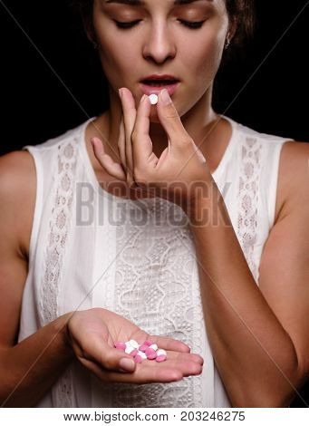 Macro picture of a female hand holding colorful tablets. A tanned girl swallows pills. A young woman in a white blouse on a black background. A heap of pills in a hand. Medicine, healthcare concept.