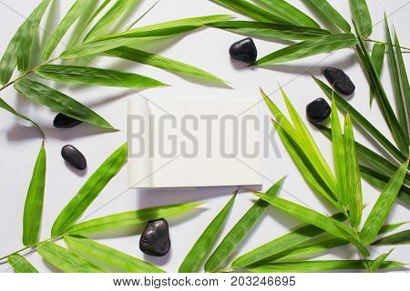 Blank page and green bamboo leaf background. White sketchbook horizontal mockup. Green bamboo leaf and sea beach pebbles flat lay. Blank paper notepad top view. Natural spa beauty banner template