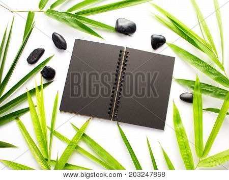 Black paper and bamboo leaf background. Black sketchbook mockup. Green bamboo leaf and sea beach pebble flat lay. Blank page notepad top view. Natural spa or beauty banner template. Tropical decor